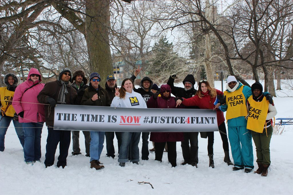Tiffany Williams, center stands with #Justice4Flint Rally members in Wilson Park
