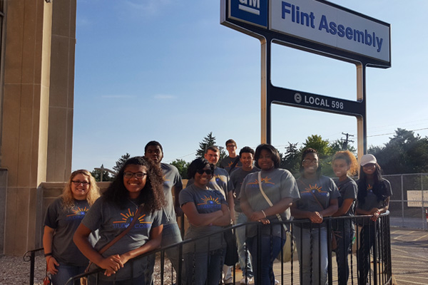 Skye Whitcomb (far left) stands with her Flint Southwestern high school students outside GM'S Flint Assembly Plant.