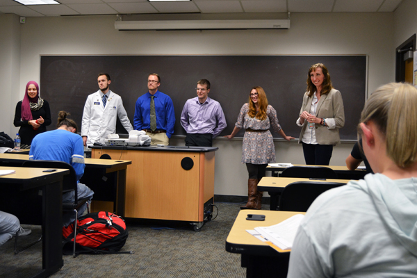 Jessica Tischler, PhD, Chair of UM-Flint's Chemistry and Biochemistry Department (standing, far right), introduces her former students.