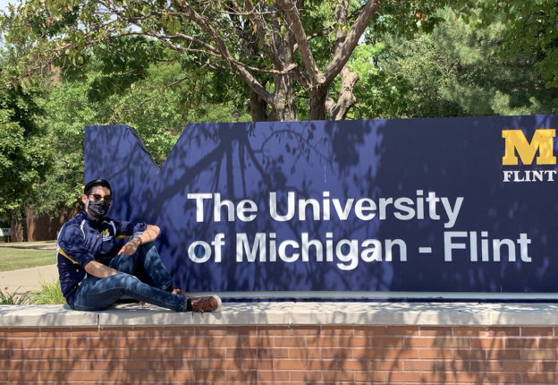 Fernando next to a UM-Flint sign
