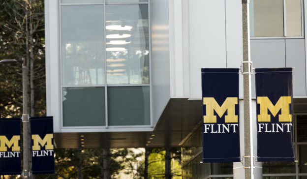A photo of a UM-Flint banner outside of the Murchie Science Building