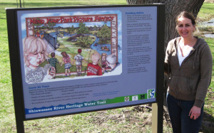 Illustrator Gayle Vandercook poses with the sign installed at Bush Park in Fenton