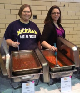 two social work volunteers serve soup at soup kitchen